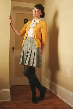 high waisted black and white check skirt, yellow cardigan, bowed tied white blouse
