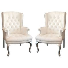 Two white wing back chairs