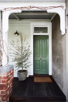 A renovated worker's cottage that maximises space and style An olive tree grows in the concrete pot, while Virginia creeper twines over the verandah. A green front door in a eucalyptus shade welcomes guests as they enter. The weatherboards have been paint Front Door Paint Colors, Exterior Paint Colors For House, Painted Front Doors, Paint Colors For Home, Green Front Doors, Exterior Front Doors, Front Door Plants, Weatherboard House, Beautiful Front Doors