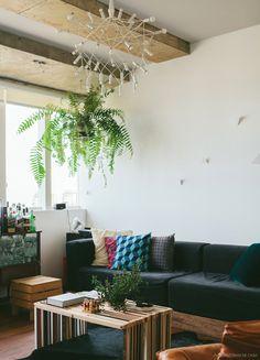 Sala de estar urbana com almofadas geométricas, plantas e instalação linda na parede.