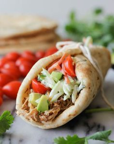 It's time to dust off that crockpot with these pulled pork gyros loaded with homemade coleslaw, avocado and cherry tomatoes.