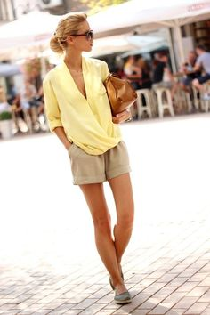 That's a smart-casual outfit that consists of deep V-neck pale yellow shirt styled with beige tailored shorts and closed-toe espadrilles.