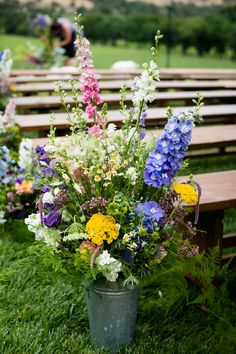 Large floral arrangements of colorful wildflowers, sunflowers, yellow and blue flowers, outdoor wedding ceremony in California, long wooden benches // Arrowood Photography