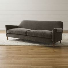 Spare sweeping lines and a lustrous low-pile velvet define this living room sofa by British designer Russell Pinch.  His signature style brings a fresh simplicity to the classic roll-arm sofa and remarkable comfort to settings formal or more casual.