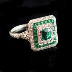 Edwardian emerald and diamond cocktail ring of square form with a central old-cut emerald with concentric borders of diamonds and emeralds to diamond-set shoulders and platinum shank English circa 1910