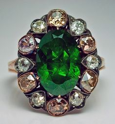 """A Russian Demantoid Garnet and Fancy Colored Diamond Cluster Ring  circa 1890, with a later shank  The ring is set with an exceedingly rare 5.1 carat Russian Ural demantoid, encircled by a single row of six white and six fancy colored old cut diamonds with an approximate total weight of 1.80 ct. The dark grass green stone is full of 'valuable' so-called """"horsetails"""",  inclusions found only in demantoids from the Urals."""
