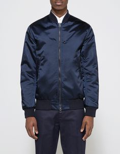 From Acne Studios, a classic bomber jacket in Navy. Featuring a ribbed collar, full zip front placket, long sleeves with ribbed cuffs, two lower front welt pockets with zipper closure, interior slit pocket, interior welt pocket with snap button closure, f