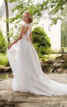 This romantic cap sleeve wedding dress with cameo back from Stella York is a sweet reminder of feminine style. Matte lace creates a shadow effect throughout the tulle skirt bringing dramatic volume and subtle interest to this A-line wedding dress. The flattering waist is drawn in by a crystal belt and deep sweetheart neckline that is finished by swirls of organic edge lace - for a truly unique dress! Fabric buttons over an easy-to-close zipper allow the butterfly lace motif to shine. This…