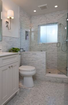 love the shower and the use of various styles of the same marble - floor may suck to clean though??? also really like the toilet placement - good idea for master bath redo in the future!