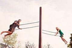 Fun engagement photo of couple on swingset - photo by Orange County based wedding photographers Mark Brooke