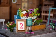 colorful centerpiece with assorted colored vintage glass, wood crate and button table numbers
