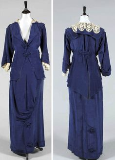Walking suit ca. 1914. Sapphire blue silk moiré. Jacket has pointed rear hem, rouleaux frogging fasteners, and floral adornments. Matching hobble skirt. Kerry Taylor Auctions