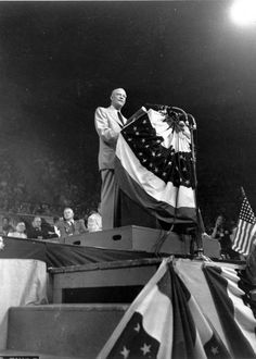 General Dwight D. Eisenhower speaking to a crowd at his homecoming celebration in Abilene, Kansas, after his retirement from active military service on May 31, 1952. Visible is an American flag and flag bunting on the speaker's podium.