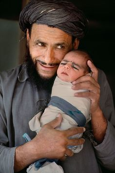 (Photo by Steve McCurry).  A proud Afghan father shows off his newborn baby and poses for a photo.  (Note -- The baby is already marked with the traditional eye make-up/ eyeliner.)