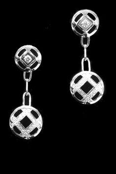 Une paire de boucles d'oreilles pendantes signée de la Maison Cartier modèle Pasha en or blanc sertie de brillants.  Hauteur des boucles : 3,3 cm  Poids brut : 9,8 grammes.   Prix à neuf : 5 100 euros.