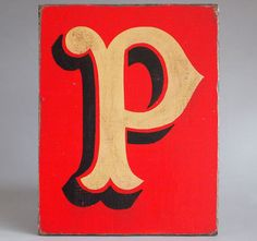 Hand-painted wooden sign: fairground letter 'P'