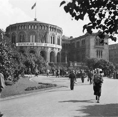 """Oslo, WWII. Stortinget (the parliament building) has been taken over by the German Reichskommiseriat, A swaztika flag has taken the place of the Norwegian flag. The banner across the building front reads """"Deutchland siegt an allen fronten""""."""