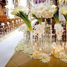 Une allée d'église plus qu'originale: la déco est simple, mais recherchée, c'est une déco réalisée par Mindy Weiss, LA weding planner des Etats Unis, de grands vases transparents avec de grandes fleurs fraiches: des callas par exemple mais pas seulement,...