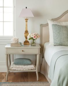 A light gray French nightstand lit by a gold leaf lamps sits between a window and a light gray wood French headboard supporting a bed dressed in blue and white bedding accented with blue pillows.
