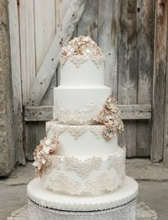 This is the type of cake I had envisioned for your wedding style - simple, white with lace appliques - more vintage elegant.  The flowers are a little rustic, but Debbie could add fresh flower accents to complement what she is providing for the decor.