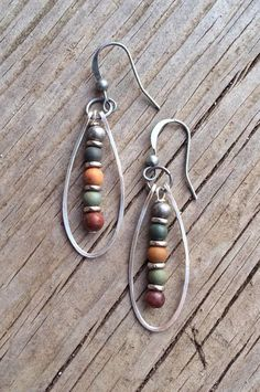"Hammered silver oval hoops with a small dangle made of natural red creek jasper and antiqued silver. Approx 1.5"" in length."