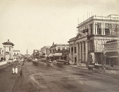 Old Court House Street - Calcutta (Kolkata) 1865 - Photographer: Oscar Mallitte Old Court House Street ran from Esplanade Row to Lal Bazaar on the eastern side of Dalhousie Square in Calcutta. This view shows one of the four ceremonial gateways to Government House on the left, which were based on designs for Adam's archways at Syon House in Middlesex, and St Andrews Church at the end of the street in Lal Bazaar. On the right of the view are commercial buildings. St. Andrew's Church is…