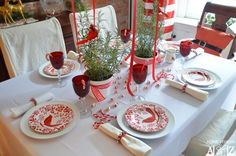 A color scheme, like this red and white one, is a great starting point. This table utilized peppermints, candy canes, and cardinals for a wintery holiday table.