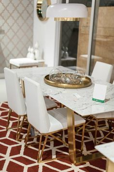 "A simple yet exquisite white marble dining table with brushed gold steel legs. - Dimensions: 78.75""L x 39.5""W x 29.75""H - Materials: Marble; Stainless Steel - Finish: White; Brushed Gold - Some light"