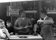"""Straatverkoper van peren, -Amsterdam, 1934. Bijschrift foto: """"hoeveel peeren wenscht mijnheer?"""" Street vendor of pears. Caption of photo: H..."""