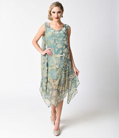 Some radiant refinery! This elegant 1920s inspired dress is a gorgeous gold burnout velvet in floral and deco designs, resting on a breezy sheer mint mesh. Boasting a graceful handkerchief hem, sleeveless style, and seamed drop waist. With a dignified sca