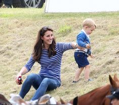 An amused Kate holds George's toy car for him as he goes for an adventurous wander up the ...