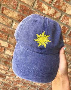 Dad hat in purple with the Tangled inspired sun embroidered on it in yellow. Want a different color hat or embroidery? Just message me! I will do my best to fulfill your requests. Hat is made from 100% washed cotton twill. It is an unstructured, 6 panel, low profile baseball cap. It has a tuck-away adjustable leather strap with an antique brass buckle, mesh lining and four rows of stitching on the bill. This is sized for adults and works for men and women.