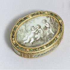 Mark of Mathieu Pionnier, Paris, 1777 Oval, the cover, sides and base with later enamelled grisaille panels depicting scenes of putti feasting on fruit within a gold chased and green enamel foliate borders, marked inside cover and base, bezel with discharge of Jean-Baptiste Fouache 21/2in. (64mm.) long.