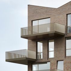 The zigzagging rooflines, handmade-brick walls and golden balconies of these London housing blocks by Duggan Morris all reference their canalside setting