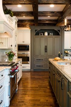 Beautiful gray and white cabinetry with a slight weathered finish matches the rustic feel of the coffered ceiling in this country kitchen. The high end appliances will keep any chef happy.