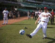 The Los Angeles Dodgers' Clayton Kershaw, left, watches as the Arizona Diamondbacks' Paul Goldschmidt, right, kicks a soccer ball at the Sydney Cricket Ground in Sydney, Wednesday, March 19, 2014. The MLB season-opening two-game series between the Dodgers and Diamondbacks in Sydney will be played this weekend. (AP Photo/Rick Rycroft)