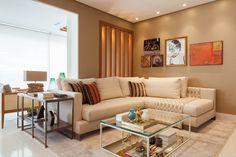 """Sala/living confortável, com sofá em """"L"""", e muitos quadros na parede! Confira mais no blog."""