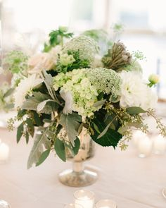 Mercury glass vases overflowed with lush arrangements of white and green hydrangeas, roses, dahlias, brunia, astilbe, ranunculus, snowberry, clematis vines, anemones, and additional greens.