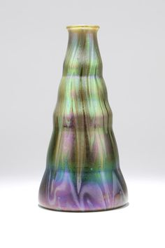 A Loetz Iridescent Art Glass Vase. Early 20th century, signed ''Loetz / Austria'', of undulating tapering form rising to a slightly flared mouth, with striations of iridescent purple and green on a spring green ground.