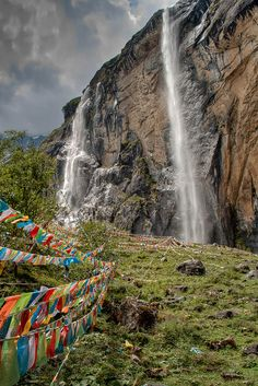 Meili Mountain Sacred Waterfall.   This is a Sacred Buddhist waterfall (美丽雪山神瀑) near Yubeng, Yunnan, China. It is an amazing place with Tibetan prayer flags everywhere and this massive waterfall with fresh water from the snow topped Meili mountain.