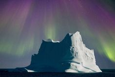 Un iceberg sous une aurore boréale au Groenland. An iceberg under the Northern Lights in Greenland.