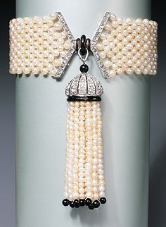 A natural pearl, enamel, and onyx tassel bracelet with diamonds set in platinum, by Mauboussin, Paris, circa 1920.