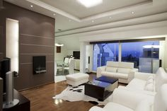 Ultra-modern living room is grounded by a natural wood floor. Bold white leather seating wraps around a black wood and glass coffee table over cow-skin rug. Large sliding glass panels lead to patio at right, while wall mounted gas fireplace sits on chocolate toned wall at left.