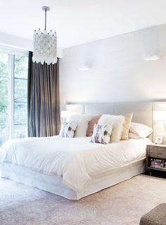 Neutral bedroom with fur pillows and grey curtains