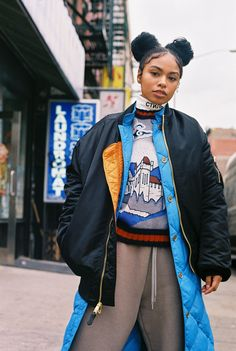 London Zhiloh, 23, in a black bomber jacket, long blue puffer jacket, white turtleneck, Gucci top with castle landscape design, and sweatpants