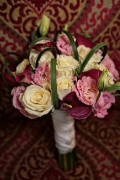 Bridal bouquet   ivory roses, pink lisianthus, pink calla lilies and lily grass loops.