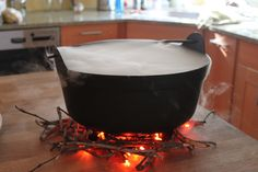 Smoking cauldron, for halloween party idea. I used a black cauldron, a string is orange Halloween lights and sticks from the yard for the fire. I used a large glass bowl and placed that inside the cauldron filled it with the punch. . The dry Ice was placed in chunks inside the cauldron not in the glass bowl. Then add small increments of hot water on top of the dry ice, smoke will really start to flow.