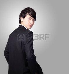 回頭看: 成功的商人微笑的臉,看著你灰色的背景,模型是亞洲男性 版權商用圖片