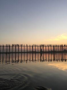 Myanmar: Silhouette of Ubein Bridge at sunset from the water.
