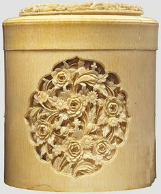 A Chinese carved ivory lidded jar circa 1840, A round turned jar with an inset base. Three exquisitely carved cartouches with figurative and floral relief ornamentation at the sides. Slip lid on the top with inset floral carving. Minor shrinkage cracks the jar slightly knocked on one side of the base. Height 11.5 cm.